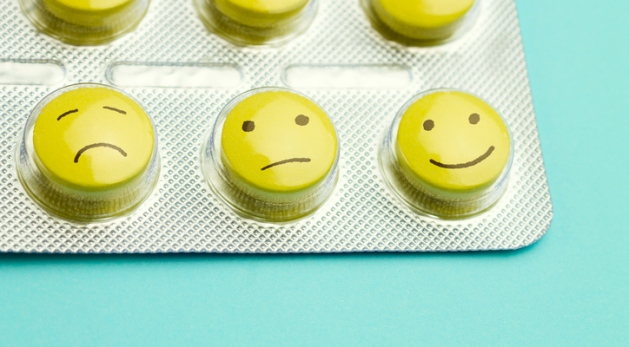 Yellow pills andfunny faces in a blister on a blue background.